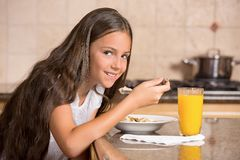 Girl eating cereal with milk drinking orange juice for breakfast Royalty Free Stock Image