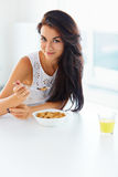 Girl eating cereal and smiling at the camera Royalty Free Stock Photos