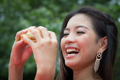 Girl Eating a Cheeseburger Stock Images