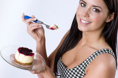 Girl eating berry topped cheesecake sweet dessert Royalty Free Stock Photography