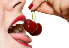 Girl eating cherries closeup. A girl, holding a pair of cherries in front of her open mouth Royalty Free Stock Photo
