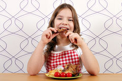 Girl eating chicken wings Royalty Free Stock Photo