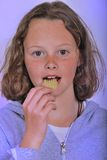Girl eating chip Stock Images