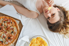 Girl eating chips on the bed, standing next to pizza Royalty Free Stock Photography