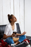 Girl eating chips, drinking soda, watching tv, sitting at sofa. Royalty Free Stock Image