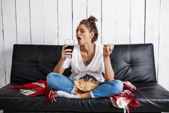 Girl eating chips, drinking soda, watching tv, sitting at sofa. Royalty Free Stock Images