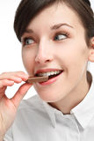 Girl eating chocolate. With smile and pleasure Royalty Free Stock Photo