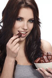 Girl eating a chocolate Royalty Free Stock Photos