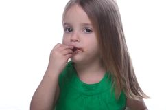 Girl eating chocolate. Girl with messy face eating chocolate Stock Images