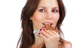 Girl eating chocolate. Portrait of young happy smiling woman eating chocolate Royalty Free Stock Photos