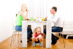 Girl eating chocolate beneath table. While the family is having breakfast Royalty Free Stock Photos