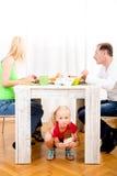 Girl eating chocolate beneath table Stock Photo