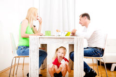 Girl eating chocolate beneath table. While the family is having breakfast Royalty Free Stock Image