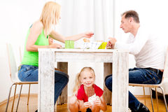 Girl eating chocolate beneath table. While the family is having breakfast Stock Images