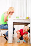 Girl eating chocolate beneath table. While the family is having breakfast Stock Image