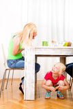 Girl eating chocolate beneath table. While the family is having breakfast Stock Photo
