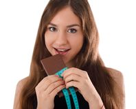 Girl eating chocolate close-up on white isolated background Royalty Free Stock Photography