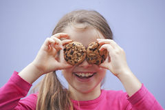 Girl eating chocolate cookies. A seven-year-old girl eating chocolate cookies Stock Photos