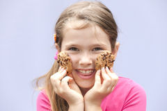 Girl eating chocolate cookies. A seven-year-old girl eating chocolate cookies Royalty Free Stock Image