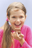 Girl eating chocolate cookies. A seven-year-old girl eating chocolate cookies Stock Photography