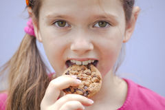 Girl eating chocolate cookies. A seven-year-old girl eating chocolate cookies Stock Images