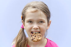Girl eating chocolate cookies. A seven-year-old girl eating chocolate cookies Royalty Free Stock Photo