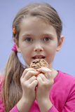 Girl eating chocolate cookies. A seven-year-old girl eating chocolate cookies Stock Photo