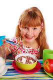 Girl eating chocolate cornflakes. Happy girl eating chocolate cornflakes Stock Photos