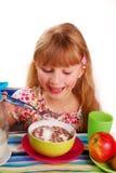 Girl eating chocolate cornflakes. Happy girl eating chocolate cornflakes Stock Photography