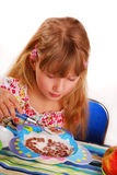 Girl eating chocolate cornflakes. Happy girl eating chocolate cornflakes Stock Photo