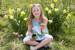 Girl Eating Chocolate Egg On Easter Egg Hunt Royalty Free Stock Photos
