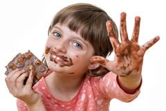 Girl eating a chocolate. A little girl eating chocolate Stock Photos