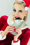 Girl eating Christmas chocolate. Girl eating a chocolate Christmas dressed in a red dress and hat Royalty Free Stock Image