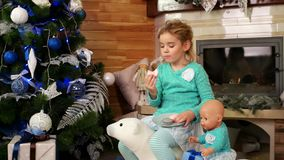 Girl eating Christmas cookies, a child plays with toys and having fun eating Cake macaron, near the fireplace and stock video