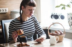 The girl is eating coffee with a croissant and checks the messages in the smartphone. Portrait Stock Photos