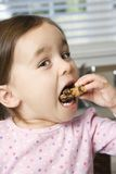 Girl eating cookie. Royalty Free Stock Photography