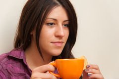 Girl Eating Cookie and Drinking Coffee Stock Image