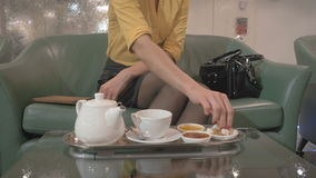 The girl eating cookie and drinking tea near the fountain in the hotel stock video footage