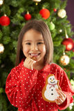 Girl Eating Cookie In Front Of Christmas Tree Royalty Free Stock Image