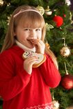 Girl Eating Cookie In Front Of Christmas Tree Stock Photos