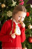 Girl Eating Cookie In Front Of Christmas Tree Royalty Free Stock Photo