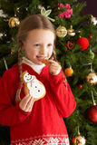 Girl Eating Cookie In Front Of Christmas Tree Royalty Free Stock Photos