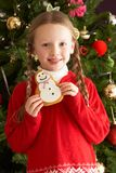 Girl Eating Cookie In Front Of Christmas Tree Stock Photography