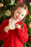 Girl Eating Cookie In Front Of Christmas Tree Stock Photo