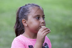 Girl eating cookie in the park Stock Photos