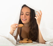 Girl eating cookies in bed. Adult girl eating chocolate chip cookies in her bed at home Stock Photography