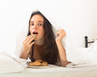 Girl eating cookies in bed Royalty Free Stock Photography