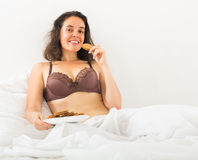 Girl eating cookies in bed Stock Photos