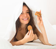 Girl eating cookies in bed Royalty Free Stock Photos