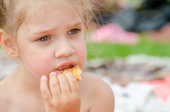 Girl eating cookies and drinking juice from a plastic disposable cup Royalty Free Stock Photo